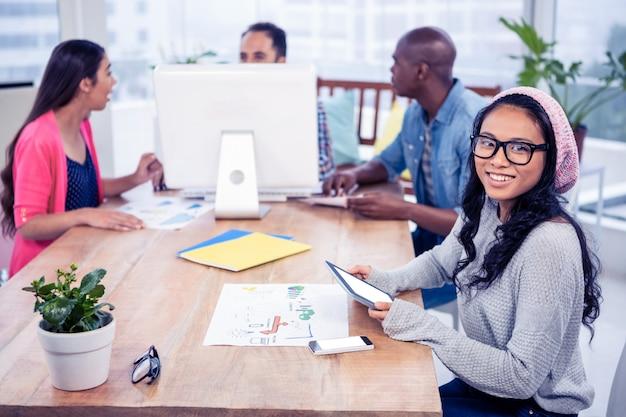 Wesoły bizneswoman gospodarstwa cyfrowego tabletu siedząc z kolegami w biurze