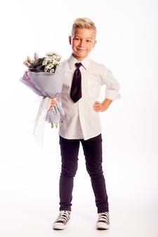 Wesoły blond chłopiec trzyma bukiet białych kwiatów na białym tle