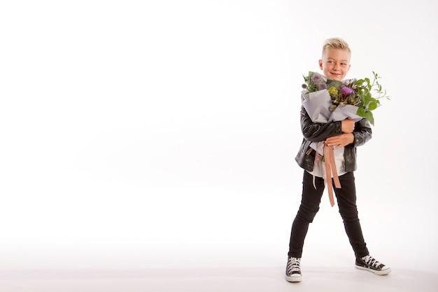 Wesoły blond modny chłopak daje bukiet na białym studio