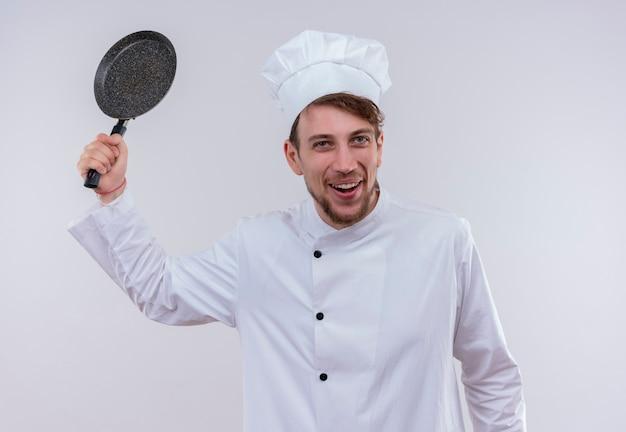 Wesoły blondynka kucharz ubrany w biały mundur kuchenki i kapelusz trzymający patelnię jak kij bejsbolowy na białej ścianie