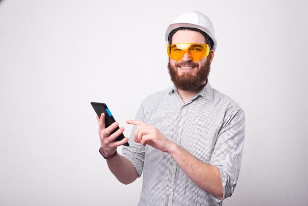 Wesoły brodaty architekt trzyma tablet i uśmiecha się do kamery ma na sobie hemlet i okulary ochronne