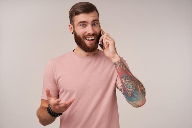 Wesoły brodaty brunet z krótką fryzurą, ubrany w codzienne ubrania i modne dodatki, stojąc na białym, prowadząc przyjemną rozmowę przez telefon i patrząc radośnie