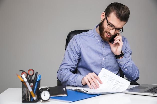 Wesoły brodaty elegancki mężczyzna w okularach rozmawiający przez smartfona i czytający coś siedząc przy stole w biurze