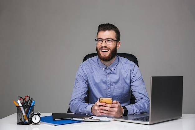 Wesoły brodaty elegancki mężczyzna w okularach siedzący ze smartfonem i odwracający wzrok
