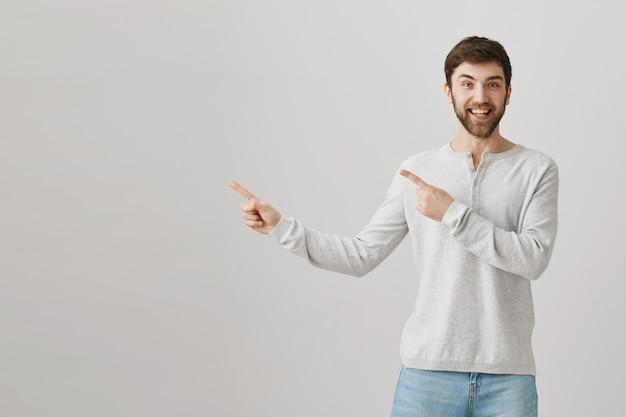 Wesoły brodaty facet kaukaski wskazując palcami w lewo