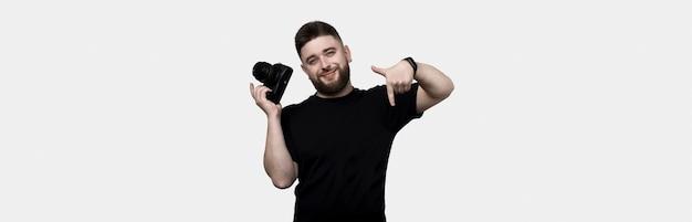 Wesoły brodaty fotograf trzyma aparat i wskazuje w dół