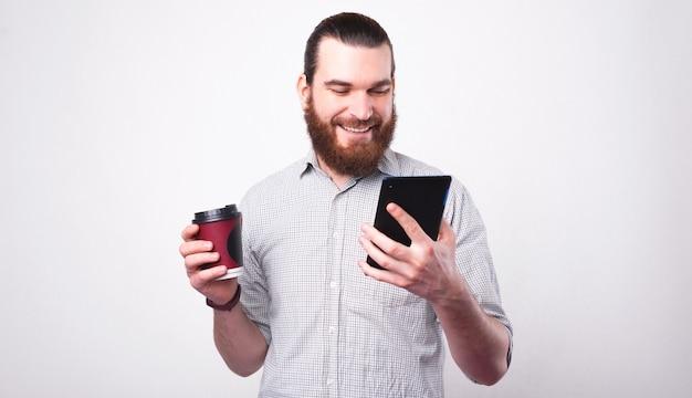 Wesoły brodaty hipster trzyma swoją kawę i rozmawia na tablecie przy białej ścianie