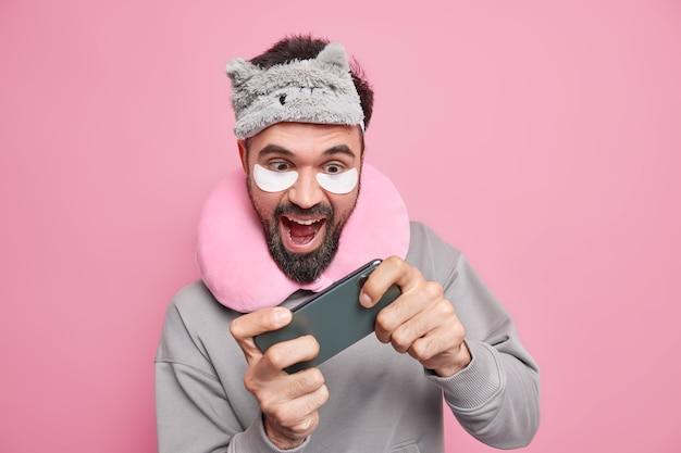 Wesoły brodaty mężczyzna gra w gry wideo na smartfonie przed pójściem spać, nosi maskę do spania i wygodną poduszkę na szyi, plastry upiększające uzależniony od nowoczesnych technologii próbuje przejść trudny poziom.