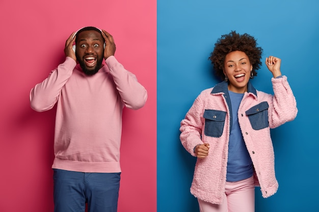 Wesoły brodaty mężczyzna nosi słuchawki stereo, śpiewa i osiąga najwyższe noty, beztroska, radosna kobieta tańczy obok, trzyma ręce uniesione, odizolowane na różowej i różowej ścianie.