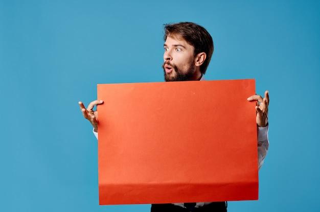 Wesoły brodaty mężczyzna trzyma czerwony sztandar niebieskie tło studio
