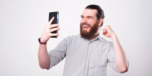 Wesoły brodaty mężczyzna trzyma tablet i patrząc na nią świętuje swoje zwycięstwo