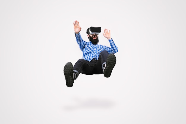 Wesoły brodaty mężczyzna w okularach wirtualnej rzeczywistości lewitujący na szarym tle