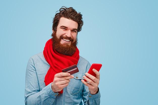 Wesoły brodaty mężczyzna za pomocą smartfona do zakupów online