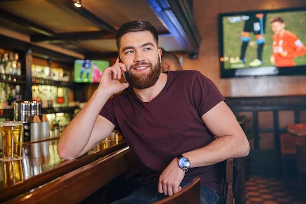 Wesoły brodaty młody mężczyzna rozmawia przez telefon komórkowy i pije piwo w pubie