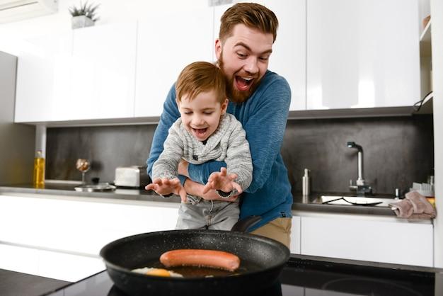 Wesoły brodaty ojciec ubrany w niebieski sweter gotuje w kuchni ze swoim małym słodkim synkiem