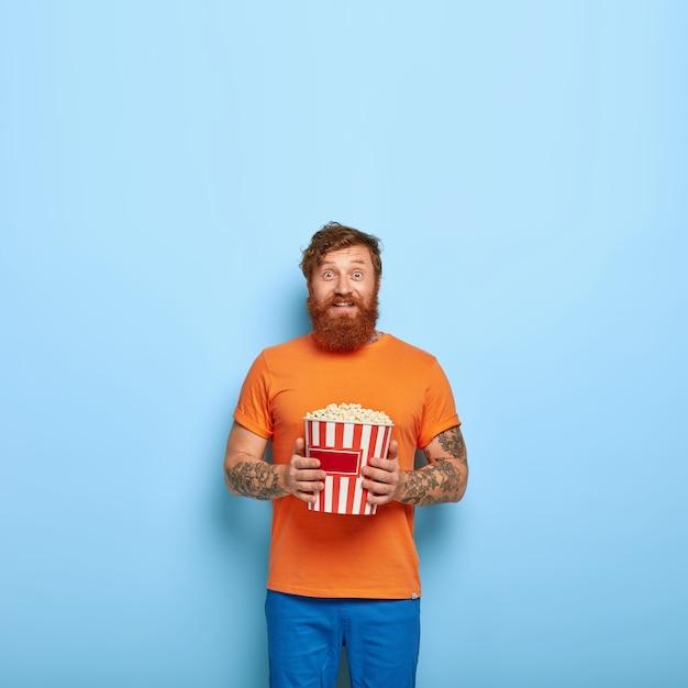 Wesoły, brodaty rudy mężczyzna je popcorn