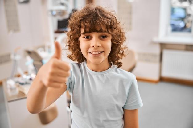Wesoły brunet w szarym t-shircie i pokazując kciuk do góry stojąc w gabinecie dentystycznym
