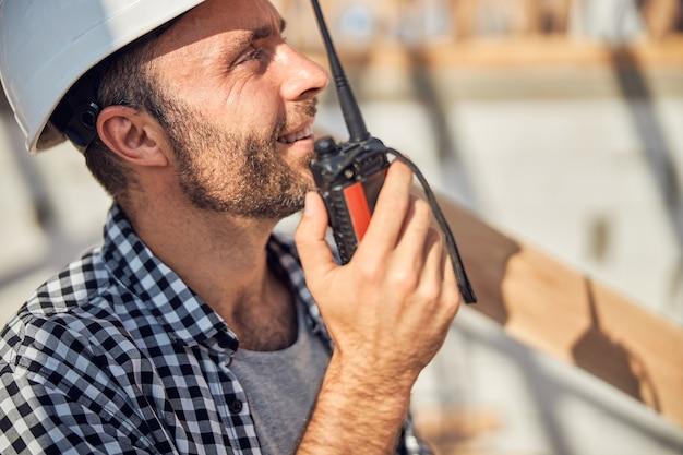 Wesoły budowniczy trzymający krótkofalówkę przy ustach