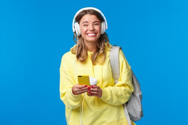 Wesoły całkiem młoda studentka z plecakiem, słuchając ulubionej playlisty w słuchawkach