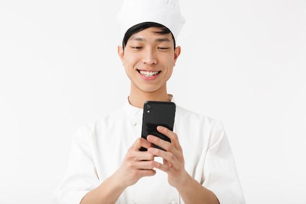Wesoły chiński wódz w białym mundurze kucharza i kapelusz szefa kuchni trzymając telefon komórkowy na białym tle nad białą ścianą