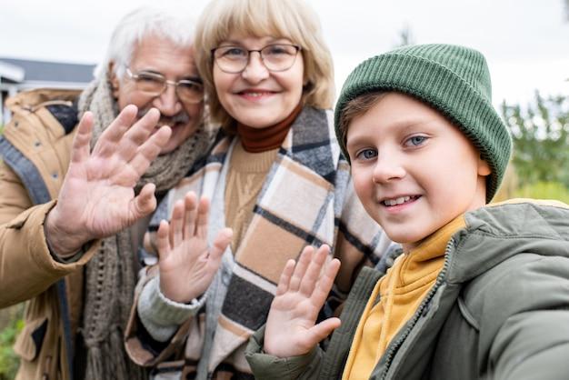 Wesoły chłopak i jego kochający dziadkowie machający rękami i patrzący w aparacie smartfona z uśmiechem podczas robienia selfie na zewnątrz