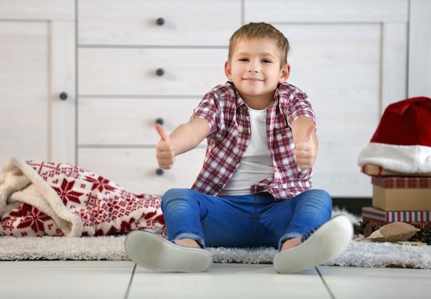 Wesoły chłopak na podłodze w udekorowanym świątecznym pokoju