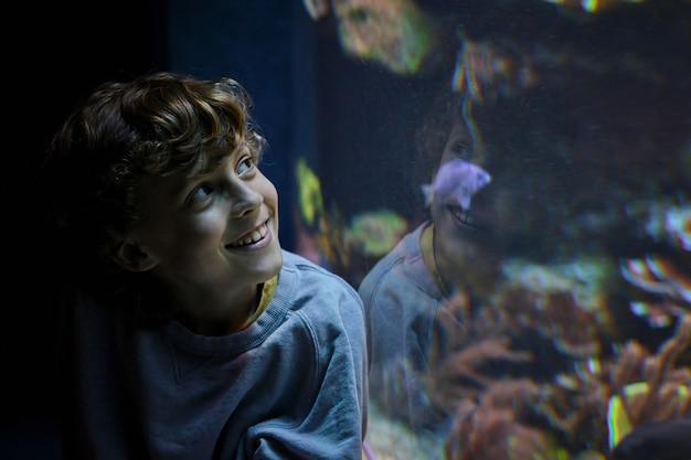 Wesoły chłopak podziwiający ryby w oceanarium