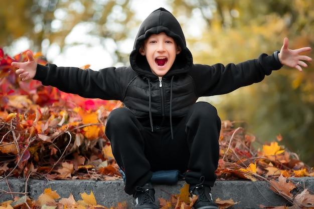 Wesoły chłopak siedzi na granicy w jesiennym pięknym parku.