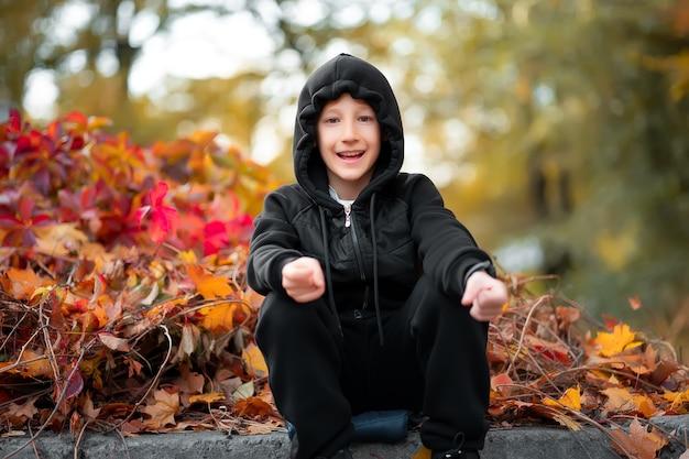 Wesoły chłopak siedzi na krawężniku w parku w pobliżu czerwonego jesiennego krzaka.