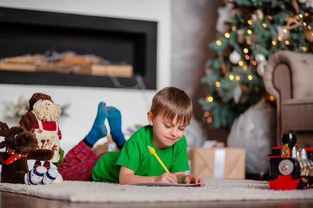 Wesoły chłopak to list do świętego mikołaja, w pobliżu choinki. szczęśliwe dzieciństwo, czas na spełnienie życzeń.