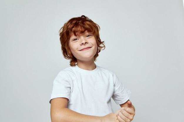 Wesoły chłopak w białym uśmiechu t-shirt trzyma ręce razem