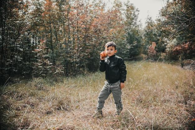 Wesoły chłopak w jesiennym lesie z jabłkiem w rękach