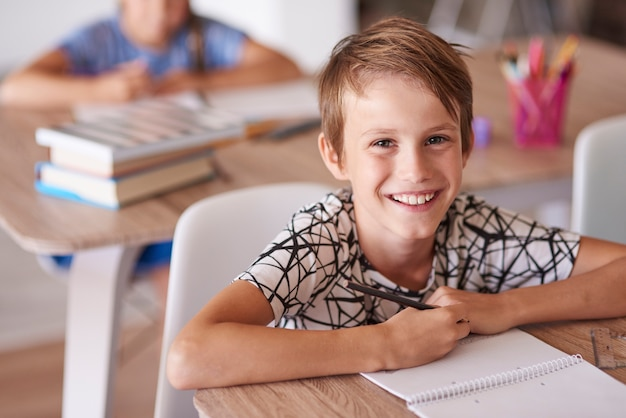 Wesoły chłopak w ławce szkolnej