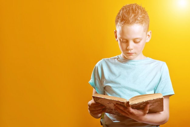 Wesoły chłopak w lekkiej koszulce trzyma książkę na kolorowym