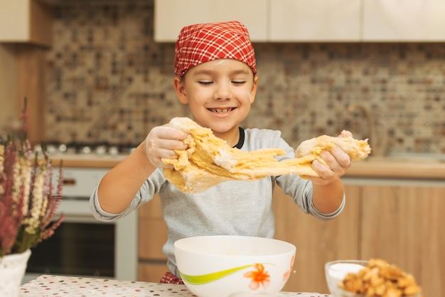 Wesoły chłopak zabawy podczas robienia ciasta na ciasteczka