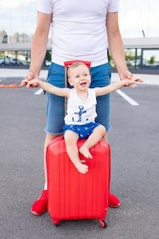 Wesoły chłopczyk siedzi na walizce z rozłożonym na boki wookiee jak samolot, koncepcja podróży lub wakacji w lecie