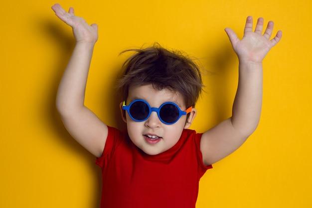 Wesoły chłopczyk w czerwonej koszulce stoi na żółtym tle w okularach przeciwsłonecznych