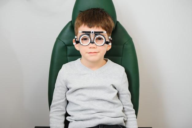 Wesoły chłopiec dziecko w okularach sprawdza wzrok okulisty dziecięcego.