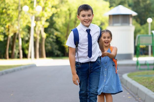 Wesoły chłopiec i dziewczynka w wieku szkolnym w białej koszuli z plecakami rano w słoneczny dzień na tle zielonego parku