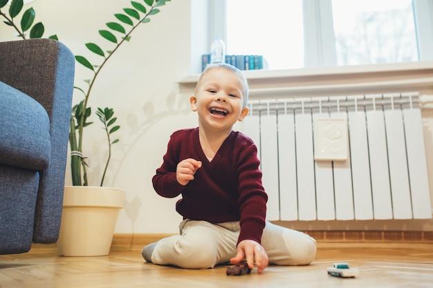 Wesoły chłopiec kaukaski siedzi na podłodze i bawi się zabawkami samochodowymi