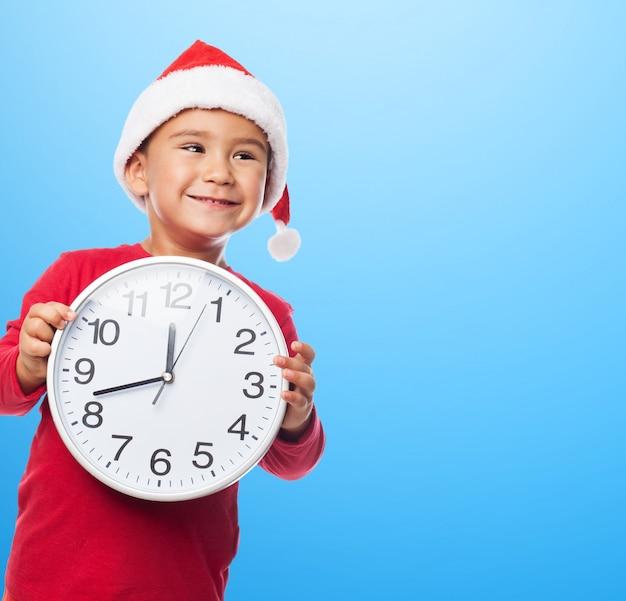 Wesoły chłopiec trzyma biały zegar z niebieskim tle