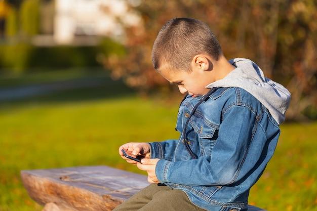 Wesoły chłopiec w dżinsowej kurtce leży na ławce i bawi się smartfonem w miejskim parku