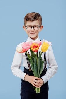 Wesoły chłopiec z bukietem kwiatów