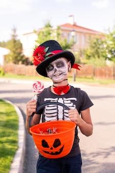 Wesoły chłopiec z pomalowaną twarzą w halloweenowej koszulce i eleganckim kapeluszu pokazujący plastikowy koszyk ze słodyczami i patrzą na ciebie