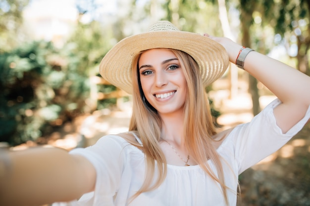 Wesoły. czas na samojebkę. młoda szczęśliwa dama na wiosennych wakacjach, spacerując po mieście, fotografując się w słoneczny dzień