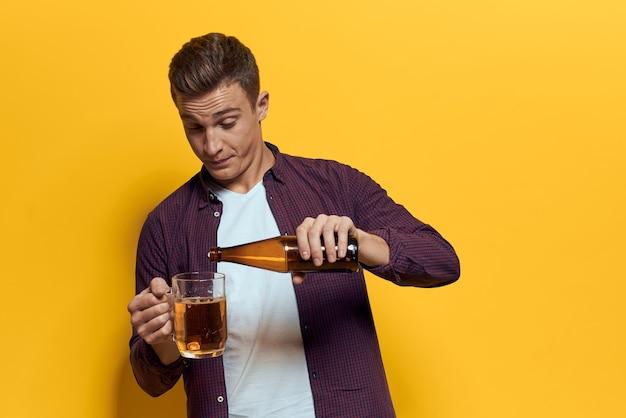 Wesoły człowiek kufel piwa z butelką zabawy pijany styl życia alkoholowy żółty. wysokiej jakości zdjęcie