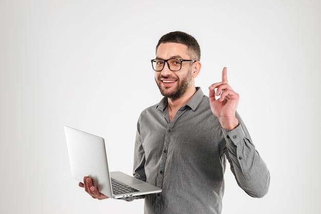Wesoły człowiek ma pomysł za pomocą laptopa.
