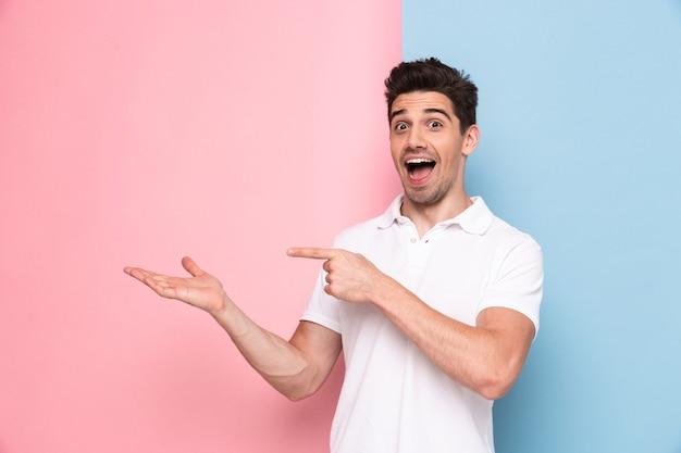 Wesoły człowiek o zarost wskazujący palce na copyspace, na białym tle nad kolorową ścianą