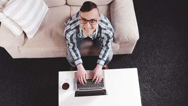 Wesoły człowiek patrząc na maszynie na laptopie