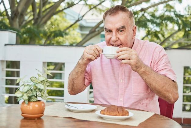 Wesoły człowiek pije kawę